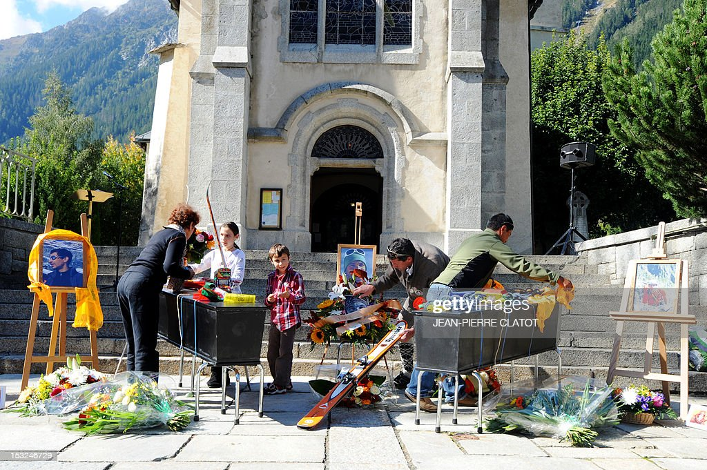 Mountain climbers put on the coffin of their colleagues Ludovic Challeat and Fabrice Priez, climbing material and Tibetan flags, during a memorial ceremony to pay tribute to the victims of the last week avalanche on Nepal's Manaslu mountain, on October 2, 2012, in Chamonix, that is considered the birthplace of European alpinism and the home of most of the French climbers killed. The four French -- two guides and two clients -- were among eight people killed after an avalanche swept through their camp on the side of the 8,156-metre (26,759-foot) Himalayan mountain, just hours before the alpinists were to make an attempt to reach the peak's summit. At left, the portrait of the climber Remy Lecluse, still missing.
