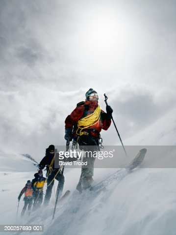 Mountain climbers walking through blizzard, linked together with rope : Stock Photo