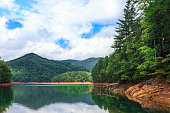 Scenic View of Fontana Lake, Great Smoky Mountains National Park, North Carolina.  Summer; daytime. Western North Carolina. WNC. Red clay visible at water's edge. Reflection in the lake.