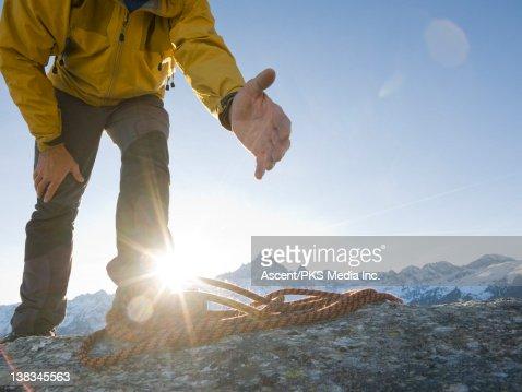 Mountain offers hand to teammate, on mnt ridge : Stock Photo