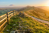 A fresh Autumnal sunrise a long The Great Ridge in the English Peak District. The image features a stone path that runs a long the ridge with a fence, bathed in vibrant golden light from the rising su