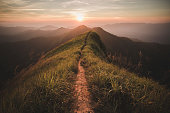 The way of climax. Mountain slope have a way for walk. Background is sunset.