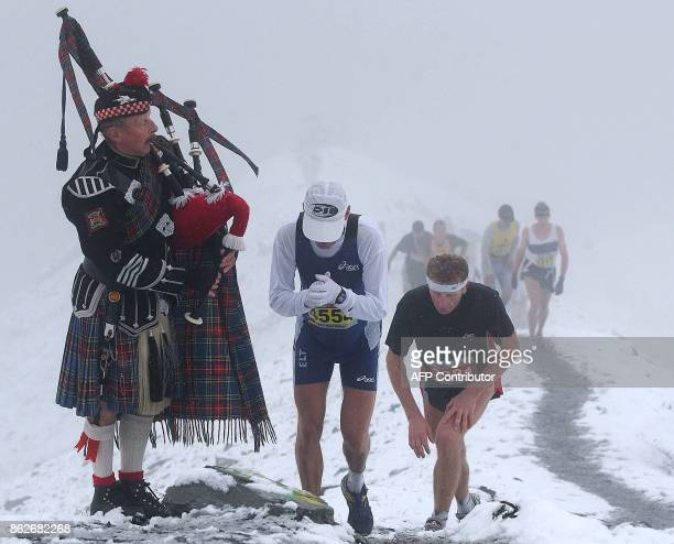'Mountain Piper' RomanAndrew Kaeslin plays his bagpipe to welcome the runners in the snow flurry near the Eiger glacier during the 9th Jungfrau...