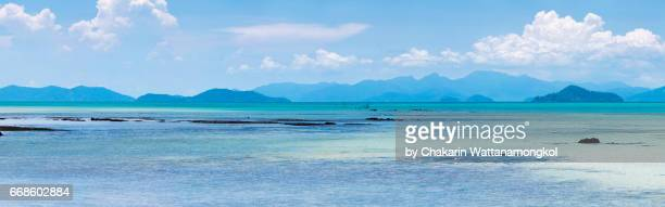 Mountain range silhouette on horizon with blue sea and cloud sky.