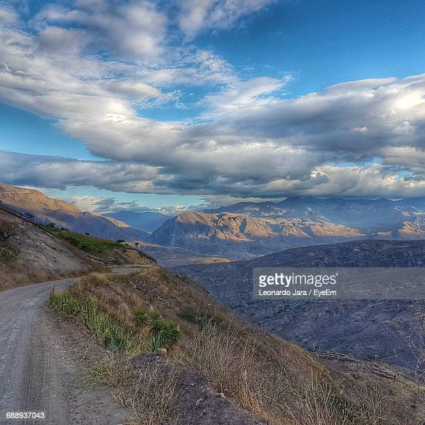 Mountain Range With Dirt Road Against Cloudy Sky