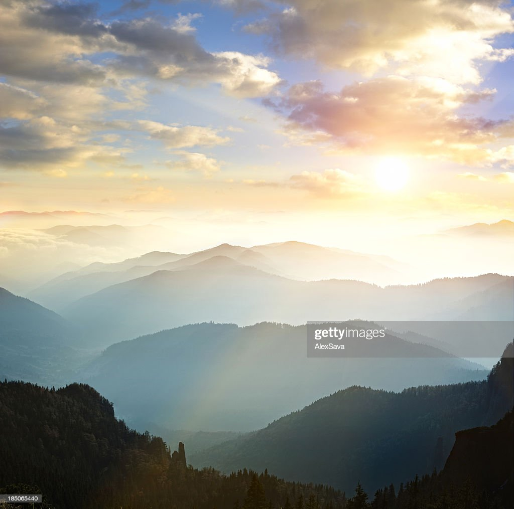 Mountain range with sun setting in background : Stock Photo
