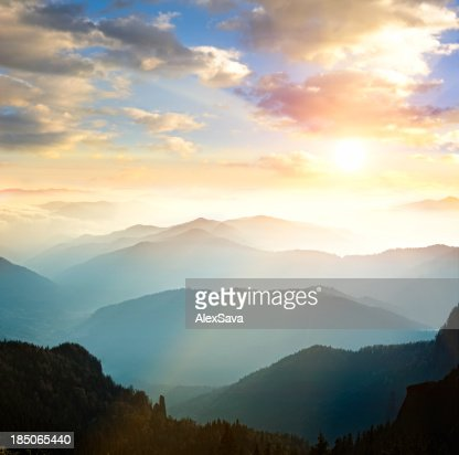 Mountain range with sun setting in background