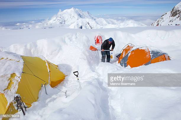 A Mountain Ranger is digging out tents after a snowstorm covered them during the night in 14k camp on Mount McKinley, Alaska.