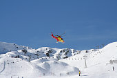 This rescue helicopter is just about taking off after picking up an injured skier (Vorarlberg/ Austria). The motion of the rotor blades is frozen. The helicopter has plates as underground stabilizers.