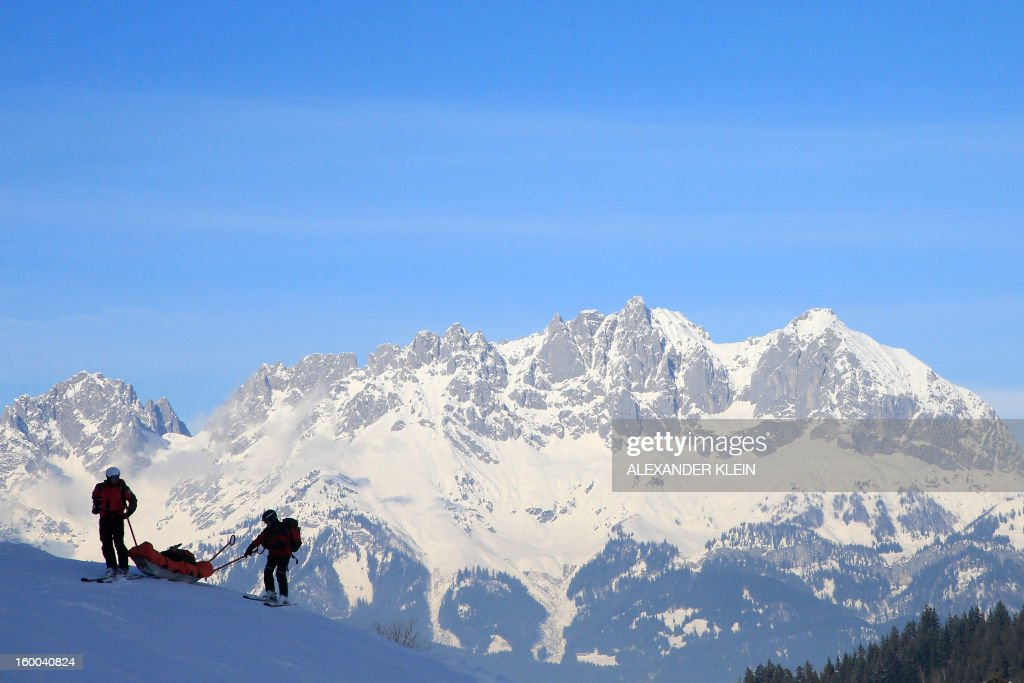 Mountain rescuers pull a sledge while rescuing a skier on the Kitzbuehel mountains, Austrian alps, on January 24, 2013.
