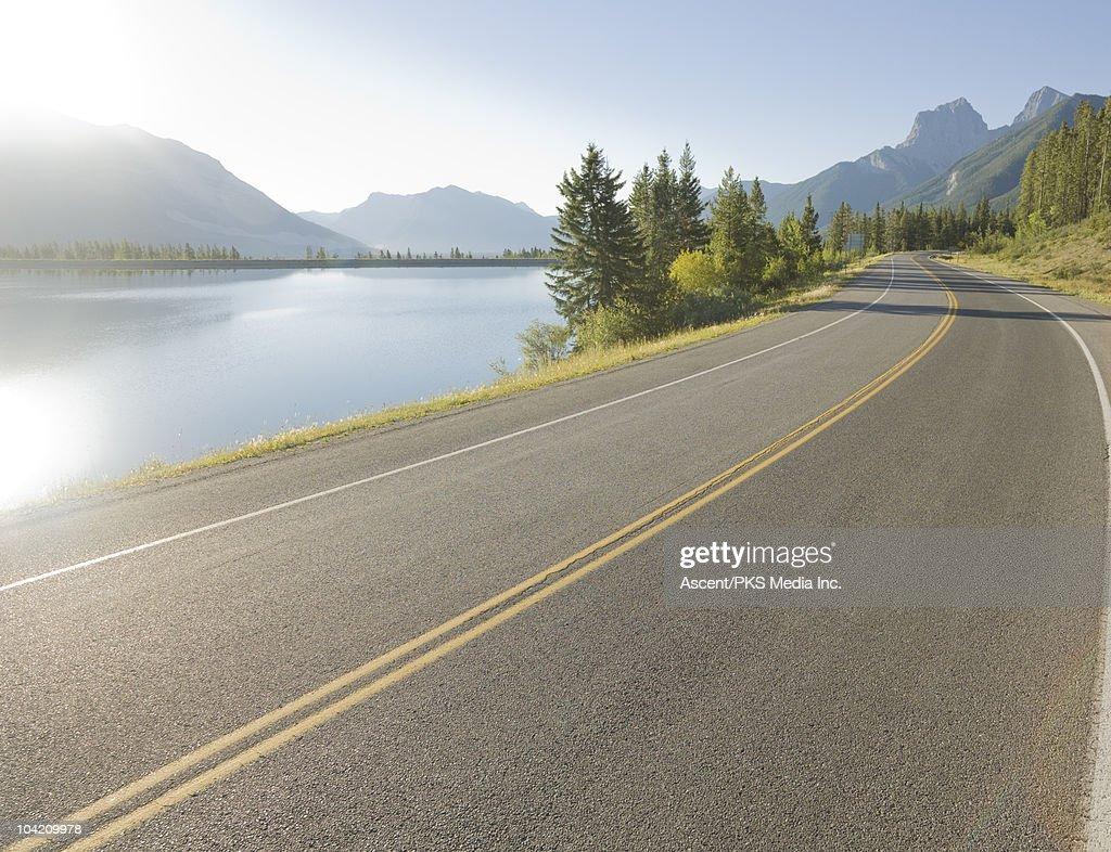 Mountain road curves around lake, in mountains : Stock Photo