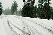 A mountain road with snow, tired tracks and oncoming cars