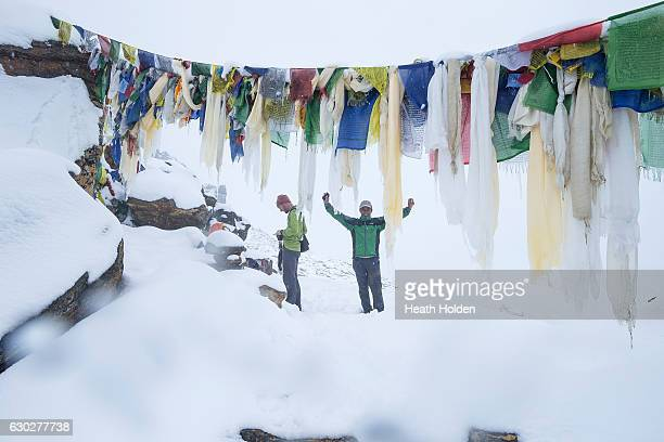 Mountain sherpa Sange Sherpa and a trekker reach the top of 5400m Renjo La Pass Ethnic Sherpas have a genetic advantage in high altitude conditions...