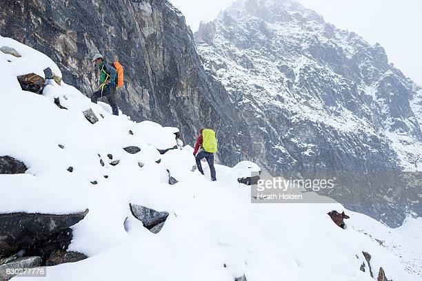 Mountain sherpa Sange Sherpa leads a trekker towards the top of 5400m Renjo La Pass Ethnic Sherpas have a genetic advantage in high altitude...