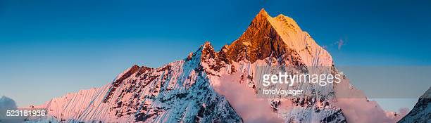 Mountain sunset golden light illuminating sacred Himalaya peak Machapuchare Nepal