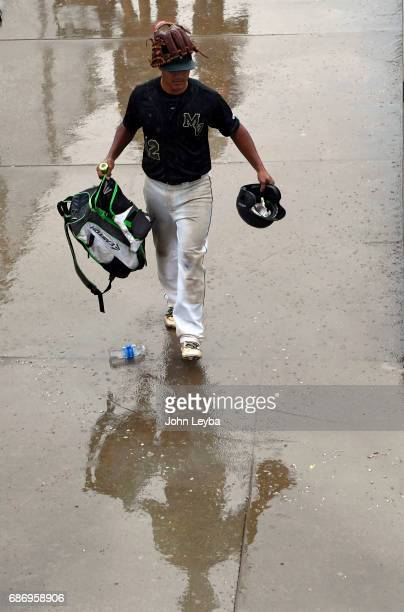 Mountain Vista Elisandro Aragon covers his head with his mitt as he navigates through the water as rain falls postponing their game with Rocky...