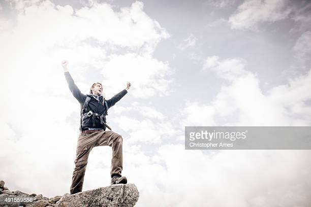 Mountain Walking Man Celebrates on Cliff Edge