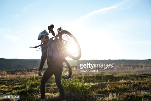 Mountainbiker carrying the bike on his shoulder : Stock Photo