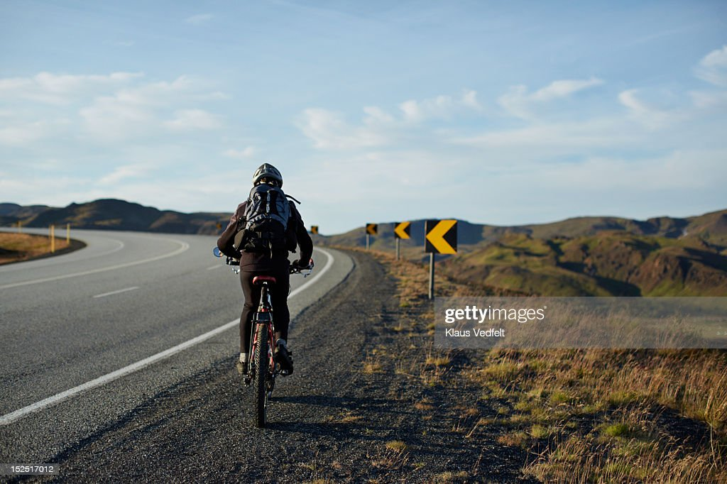 Mountainbiker cycling uphill on big road : Stock Photo