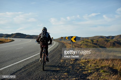 Mountainbiker cycling uphill on big road : Stock Photo