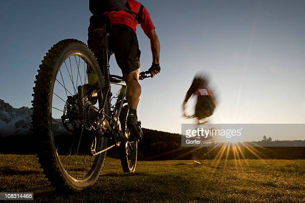 mountainbiker in rapidlyer goes direction sunset