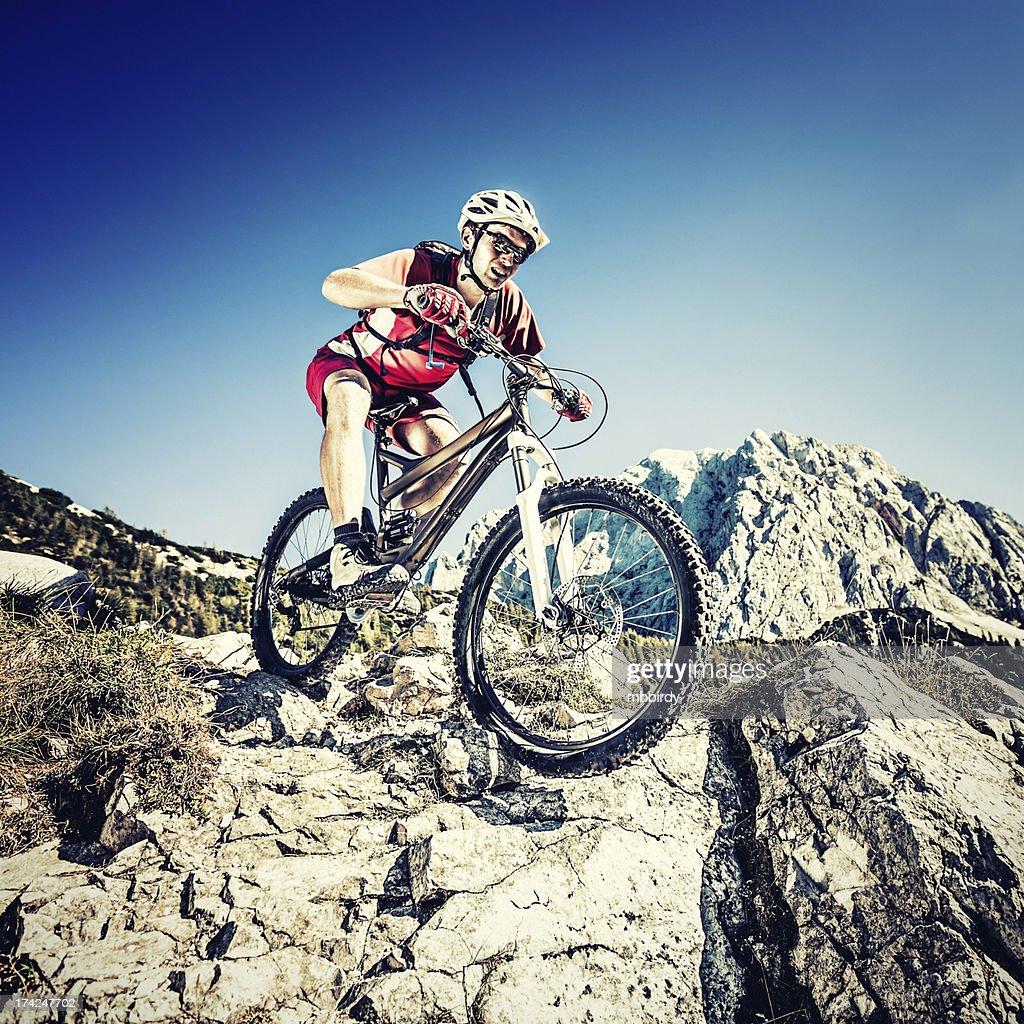 Mountainbiker on steep trail : Stock Photo