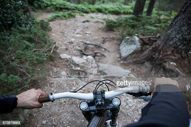 Mountainbiker riding downhill on rocky path in a forest