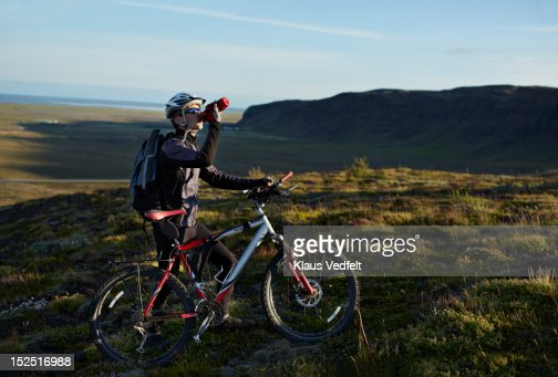 Mountainbiker taking a drinking brake on the hill : Stock-Foto