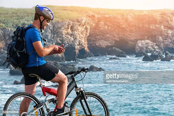 Mountainbiker using smart phone on rock