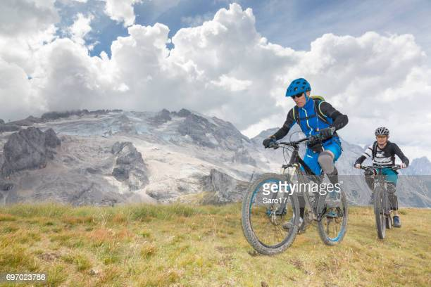 Mountainbiking in front of Mt. Marmolada, Dolomites, Italy