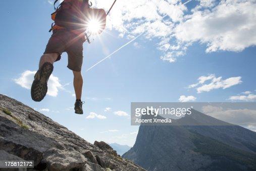 Mountaineer bounds across rock ridge, mtns below