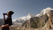 Mountaineer drinking with peak Masherbum at bottom