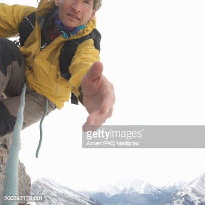 Mountaineer extending hand on mountainside, close-up : Stock Photo