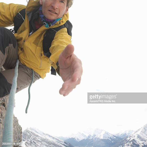 Mountaineer extending hand on mountainside, close-up