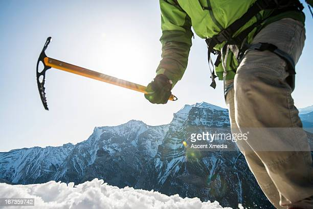 Mountaineer grips ice axe while ascending slope
