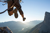 Mountaineer in mid air leap above mountains