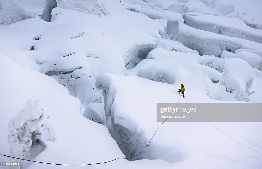 Mountaineer in snow trying to find a way around crevasses : Stock Photo