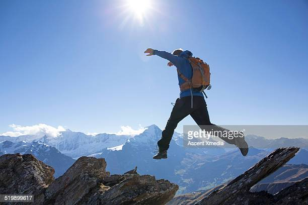 Mountaineer jumps between rocks on mountain ridge