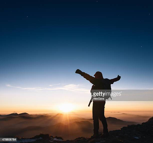 Mountaineer outstretching his arms on top of the mountain