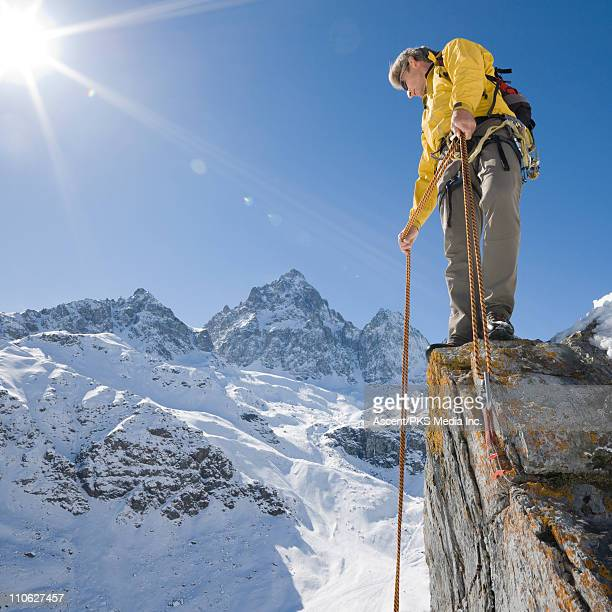 Mountaineer prepares to step off cliff, abseiling