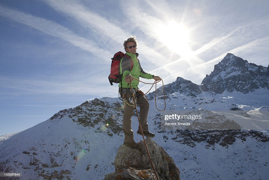 Mountaineer pulls rope tight to teammate : Stock Photo