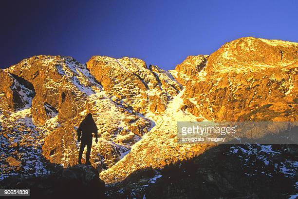 mountaineer silhouetted against sunset mountains
