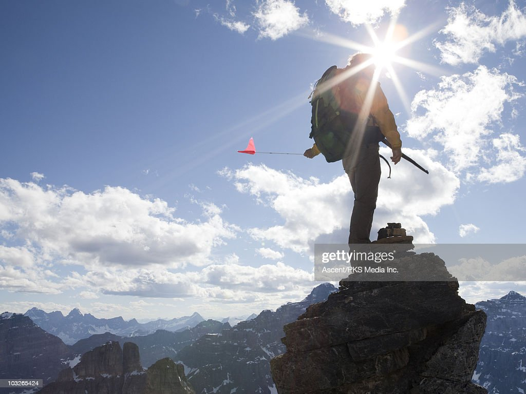 Mountaineer stands on mtn summit, holds flag : Stock Photo