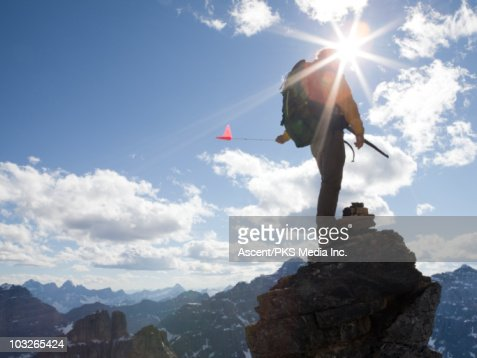 Mountaineer stands on mtn summit, holds flag : Stockfoto
