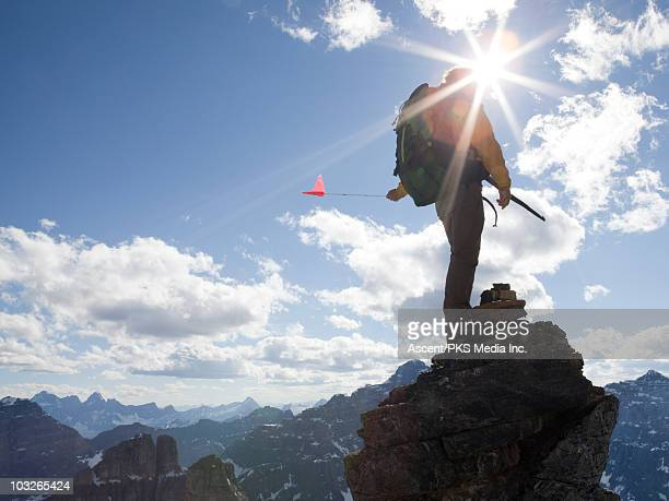 Mountaineer stands on mtn summit, holds flag