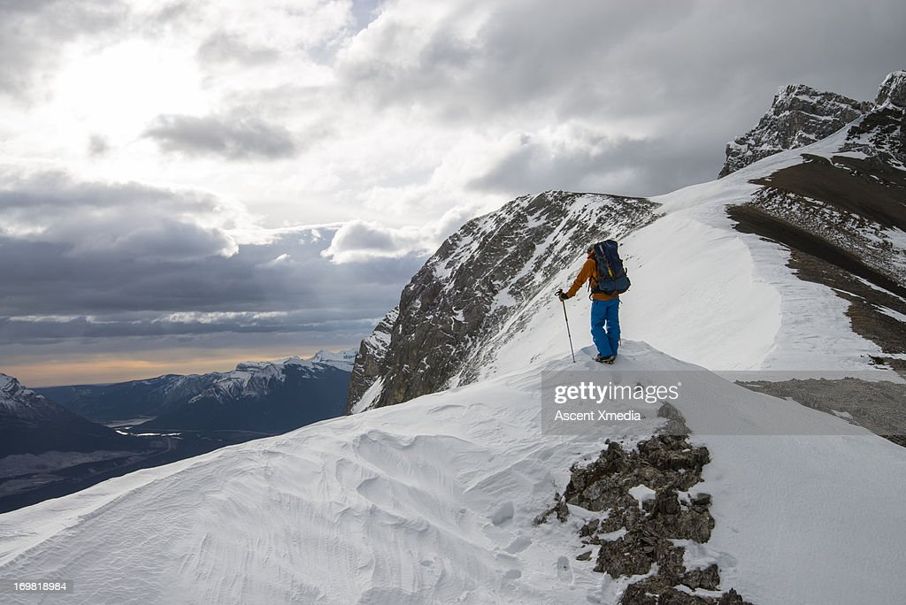 Mountaineer stands on ridge crest, looks out : Stock Photo