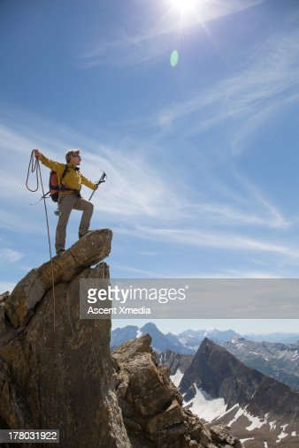 Mountaineer stands on summit, arms outstretched : Stock Photo