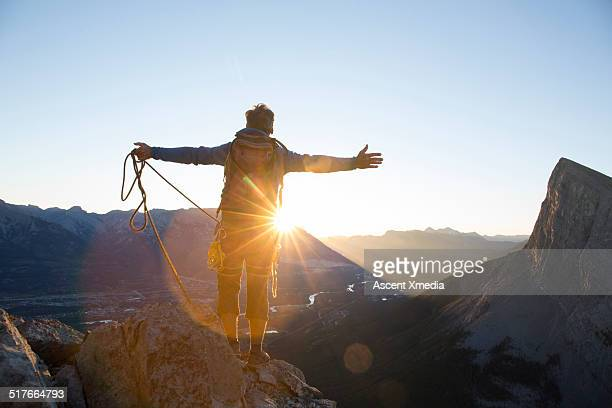 Mountaineer stands on summit at sunrise, arms out