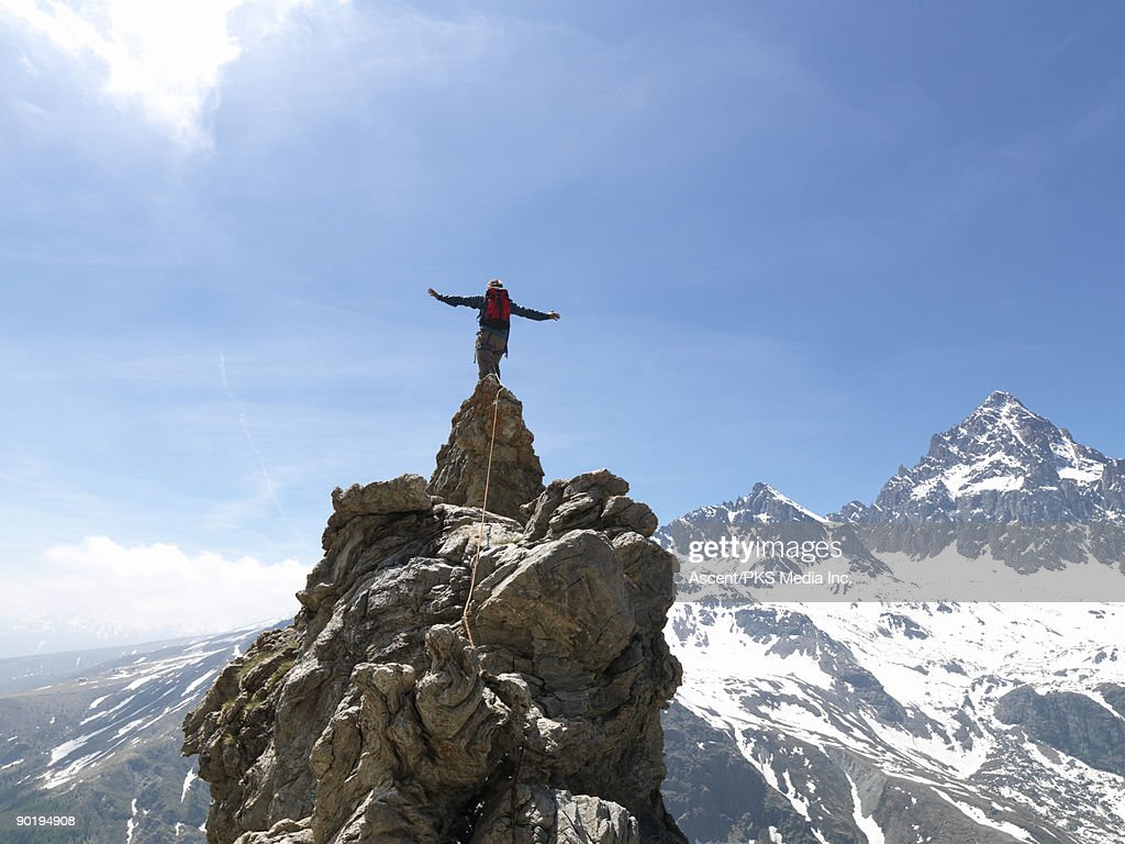 Mountaineer stands on top of pinnacle, mtns below : Stock Photo