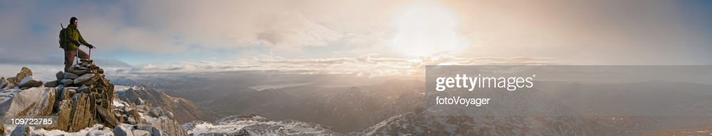 Mountaineer sunrise snow summit golden dawn panorama Lake District UK : Stock Photo